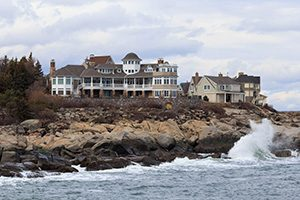 Large vacation home overlooking waves crashing on rocky shore in York, Maine